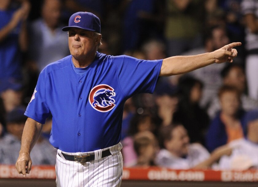 FILE - In this July 12, 2009, file photo, Chicago Cubs manager Lou Piniella signals for pitcher Sean Marshall to come back from left field to pitch in the ninth inning of the second game of a baseball doubleheader against the St. Louis Cardinals in Chicago. Cubs manager Joe Maddon gained attention