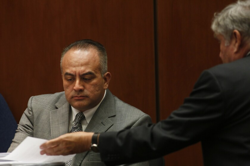 California Assemblyman Raul Bocanegra (D-Pacoima), left, is shown a document by defense attorney Richard P. Lasting during the perjury and voter fraud trial of Richard Alarcon and his wife, Flora Montes de Oca Alarcon, in Los Angeles District Court on Tuesday.