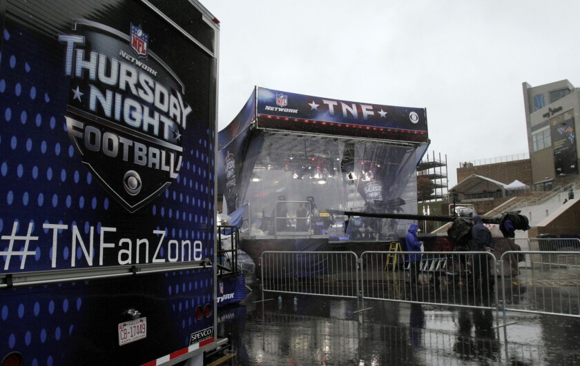 """The NFL Network's """"Thursday Night Football"""" studio set, protected from heavy rain, sits outside Gillette Stadium before a game between the New England Patriots and the New York Jets."""