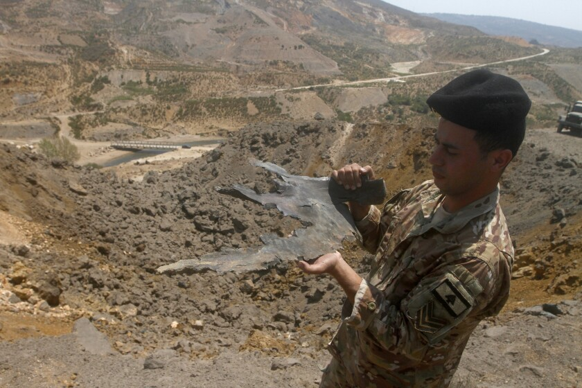 A Lebanese army soldier displays part of an Israeli missile from an airstrike in Dimashqiya farmlands, southern Lebanon, Thursday, Aug 5, 2021. Israel on Thursday escalated its response to rocket attacks this week by launching rare airstrikes on Lebanon, the army and Lebanese officials said. (AP Photo/Mohammed Zaatari)