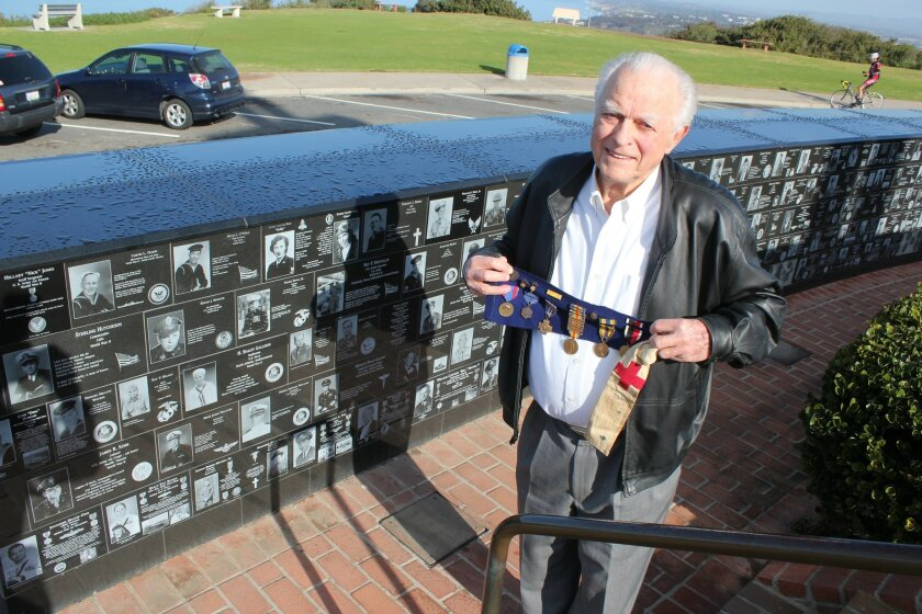 Bill Mitchell stands beside a memorial plaque dedicated to his parents, an Army combat medic and nurse who met during World War I. In his hands are his father's once blood-soaked armband and medals, including one with six bars denoting each of the battles his father served in during WWi. Pat Sherman