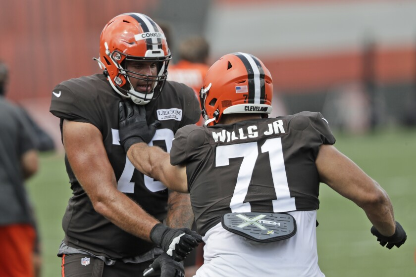 Cleveland Browns offensive tackles Jedrick Wills Jr., right, and Jack Conklin work on a drill during practice at the NFL football team's training camp facility, Thursday, Aug. 27, 2020, in Berea, Ohio. (AP Photo/Tony Dejak)