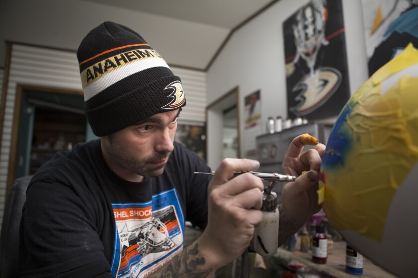Noah Ennis, a helmet and hockey mask painter, works on a design in his shop, Shell Shock Custom Paint, in Fairbury, Neb.