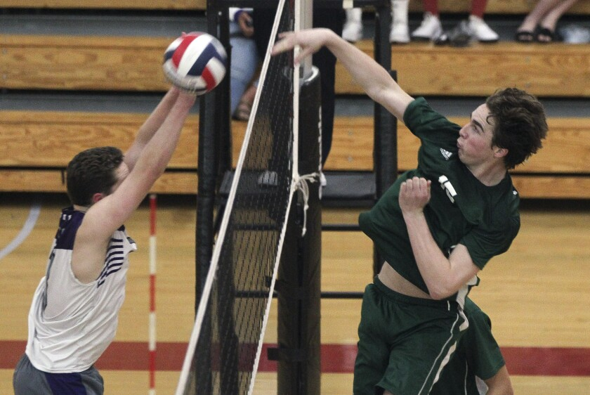 Poway's Tanner Swindall (right) hits the ball toward Carlsbad's Zach Knudsen in the San Diego Section Division I title match Saturday. The Titans won in five sets.