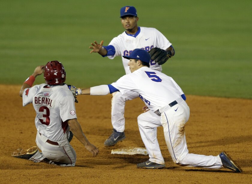 Florida's Dalton Guthrie (5) tags Arkansas' Michael Bernal (3) as he slides into second base during the fourth inning of a Southeastern Conference college baseball tournament game, Wednesday, May 20, 2015, in Hoover, Ala. (AP Photo/Butch Dill)