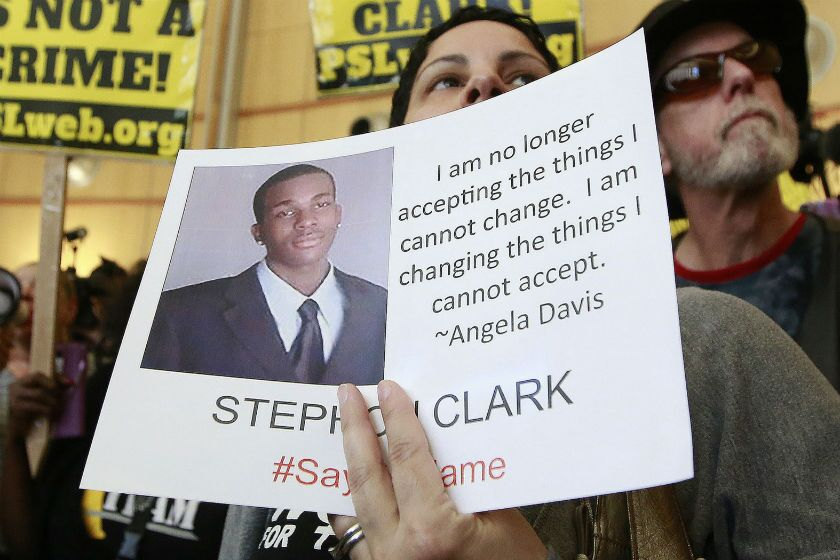 A woman displays a photo of Stephon Clark during a protest in Sacramento in 2018.