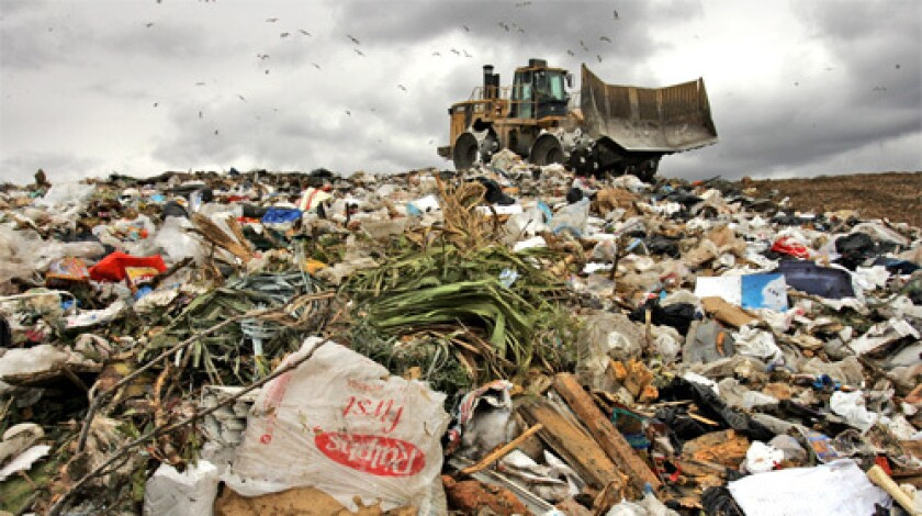 PART OF THE SCENE: A plastic grocery store bag lies amid trash at a Calabasas landfill. Environmentalists argue the county's 6 billion plastic bags litter streets and harm marine life.