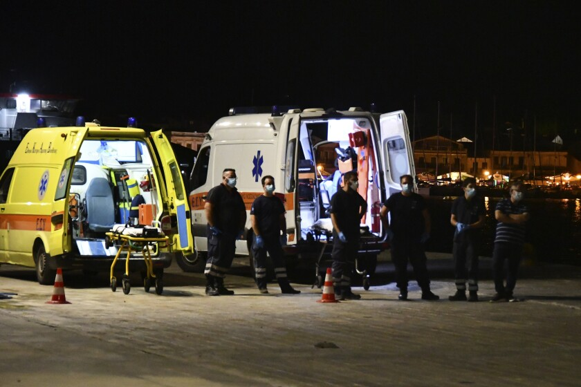 Paramedics wait next to ambulances at Pythagorio port, on the eastern Aegean island of Samos, Greece, late Monday, Sept. 13, 2021. A small private plane crashed into the sea off Greece's eastern Aegean Sea island of Samos late Monday killing both people on board, the Greek coast guard said. State ERT TV said the victims were a man and a woman from Israel who had been planning to visit the island. There was no information on their identities. (AP Photo/Michael Svarnias)