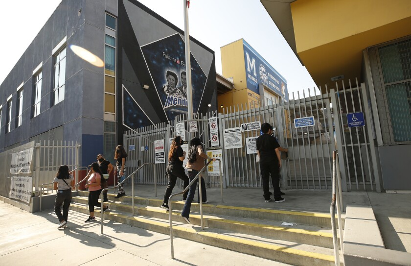 Students walk up steps to school gates