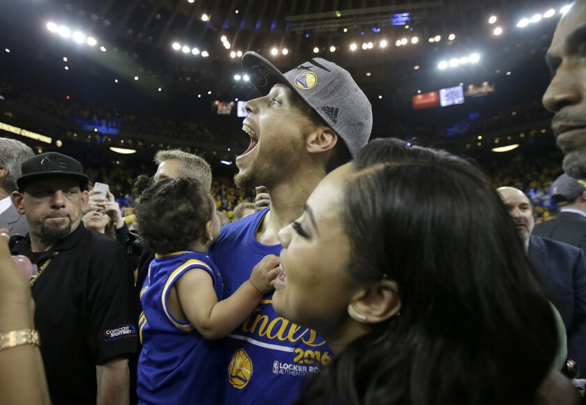 Golden State Warriors guard Stephen Curry, center, and his wife Ayesha celebrate after the Warriors beat the Oklahoma City Thunder in Game 7 of the NBA basketball Western Conference finals in Oakland, Calif., Monday, May 30, 2016. The Warriors won 96-88. (AP Photo/Marcio Jose Sanchez, Pool)