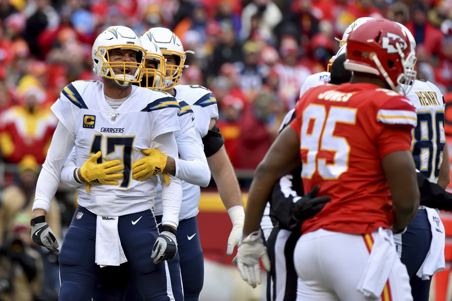 Los Angeles Chargers quarterback Philip Rivers (17) is held back by a teammate as he yells at Kansas City Chiefs defensive tackle Chris Jones (95) during the first half of an NFL football game in Kansas City, Mo., Sunday, Dec. 29, 2019. (AP Photo/Ed Zurga)