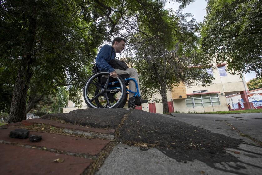 David Radcliff crossing a warped sidewalk in his wheelchair