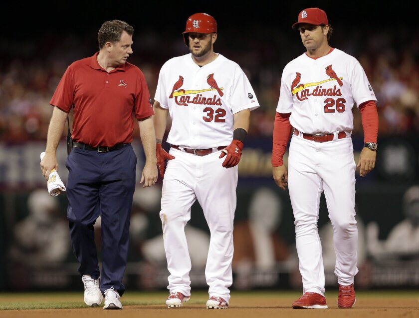St. Louis Cardinals' Matt Adams, center, walks off the field after being checked on by Cardinals trainer Chris Conroy, left, and manager Mike Matheny after an injury during the fifth inning of a baseball game against the Arizona Diamondbacks Tuesday, May 26, 2015, in St. Louis. Adams left the game after injuring his right leg while running out a double. (AP Photo/Jeff Roberson)