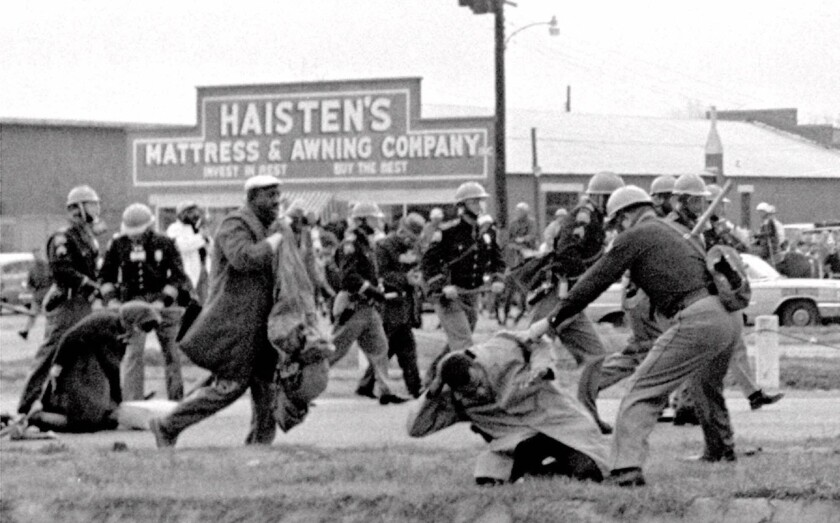 "Alabama state troopers swing nightsticks to break up the ""Bloody Sunday"" voting march in Selma, Ala., on March 7, 1965. John Lewis, front right, of the Student Non-violent Coordinating Committee, is put on the ground by a trooper."