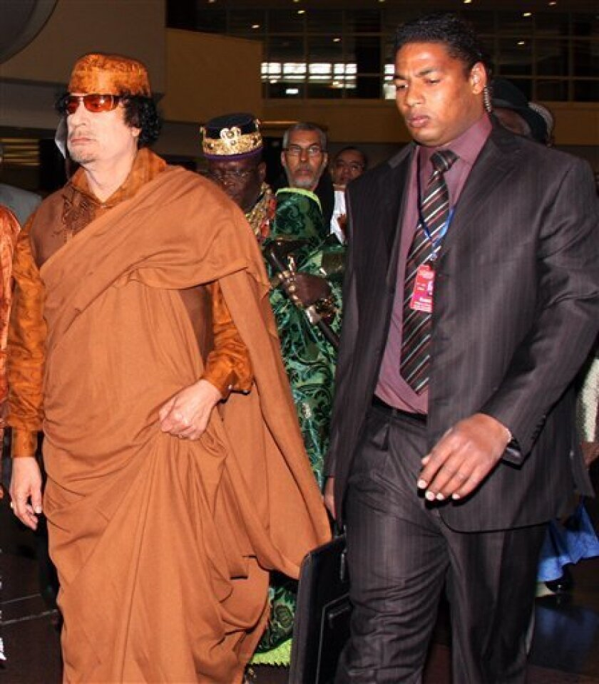 """Libyan leader Moammar Gadhafi, left, escorted by bodyguard, right, arrives at the African Union Meeting in Addis Ababa, Sunday, Feb. 1, 2009. Gadhafi has been elected to lead the African Union, a position that will give the eccentric and often erratic head of state the power to guide policy across Africa. The Libyan leader, who last year declared himself the """"king of kings"""" in Africa and whose official title in Libya is """"Brotherly Leader and Guide of the Revolution,"""" told some 20 African heads of state gathered for an annual summit that he would work to unite the continent into """"the United States of Africa.""""(AP Photo/Samson Halieyesus)"""