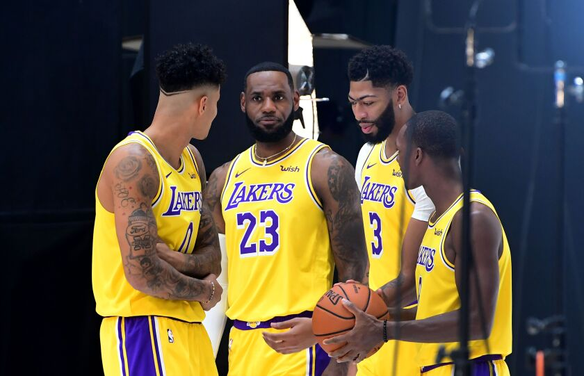 LeBron James and his Lakers teammates (left to right) Kyle Kuzuma, Anthony Davis and Rajon Rondo prepare for a photo shoot.