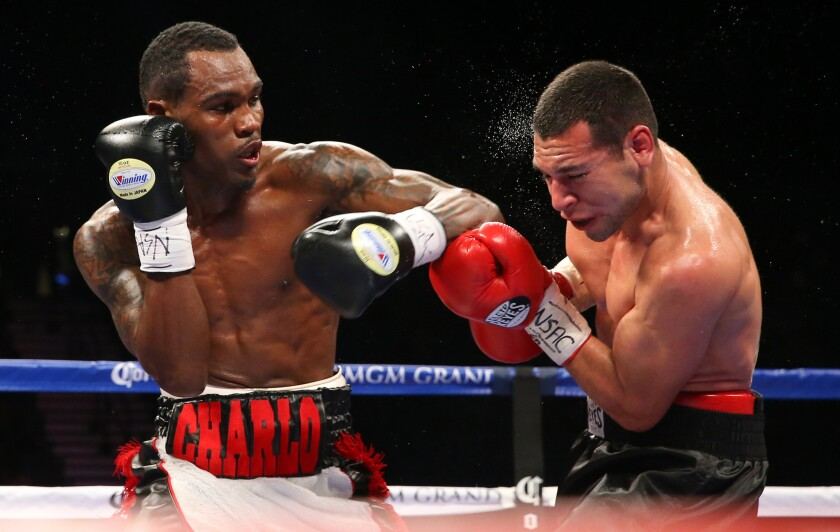 Jermell Charlo, left, trades punches with Mario Lozano on Dec. 13, 2014 in Las Vegas.