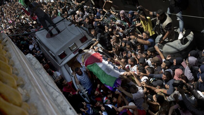 Palestinian mourners carry the body of a volunteer paramedic Razan Najjar, 21, into her family house
