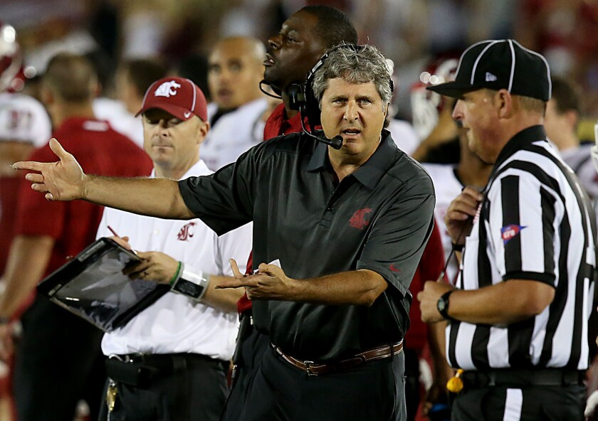 Washington State Coach Mike Leach talks with an official in the fourth quarter of a game against USC on Sept. 7, 2013.