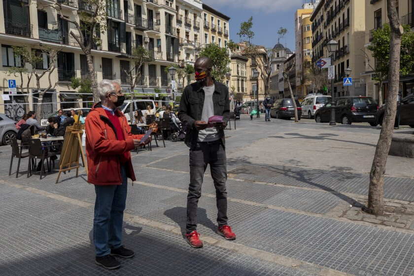Serigne Mbaye, who is running on a ticket with the anti-austerity United We Can party, in the Madrid regional assembly elections, talks with a potential voter during an election campaign event in Madrid, Spain, Friday, April 16, 2021. Mbaye, a Senegalese-born environmental refugee wants to defy a history of underrepresentation of the Black community and other people of color in Spanish politics. Serigne Mbaye's candidacy has been met with a racist response from an increasingly influential far-right political party. (AP Photo/Bernat Armangue)