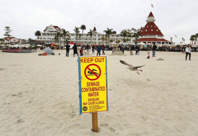 Signs warn beachgoers to avoid contact with ocean water after recent rains elevated bacteria levels in Coronado, and surrounding beaches on Dec. 29, 2019.  The Hotel del Coronado is in the background.