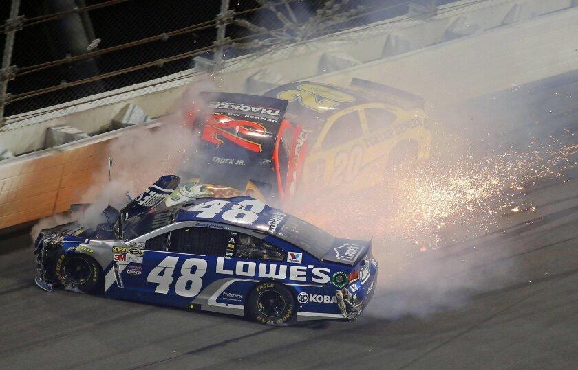 Jimmie Johnson (48), Martin Truex Jr (78) and Matt Kenseth (20) crash during the second of two qualifying races for Sunday's NASCAR Daytona 500 Sprint Cup series auto race at Daytona International Speedway in Daytona Beach, Fla., Thursday, Feb. 18, 2016. (AP Photo/John Moore)