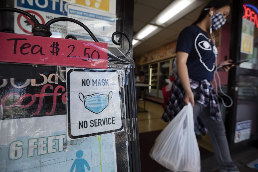 """A """"no mask, no service"""" sign at a Chinatown business."""