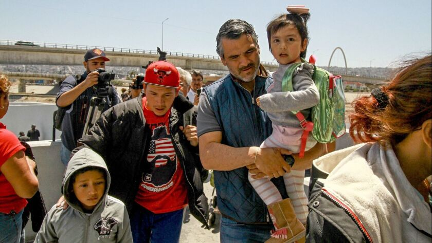 Central American migrants cross into the United States at the El Chaparral border crossing, in Tijuana, Mexico, on May 4.