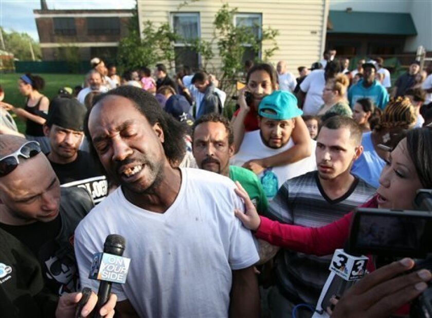 Neighbor Charles Ramsey speaks to media near the home on the 2200 block of Seymour Avenue, where three missing women were rescued in Cleveland, on Monday, May 6, 2013. Cheering crowds gathered on the street where police said Amanda Berry, Gina DeJesus and Michele Knight, who went missing about a decade ago and were found earlier in the day. (AP Photo/The Plain Dealer, Scott Shaw)