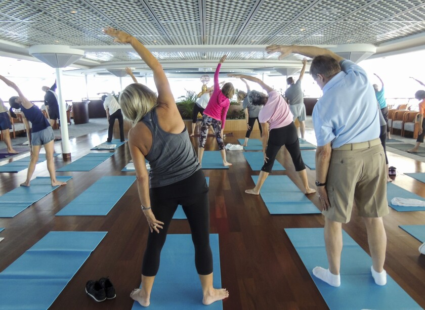 Passengers stretch during a yoga class aboard the Crystal Serenity. Yoga is