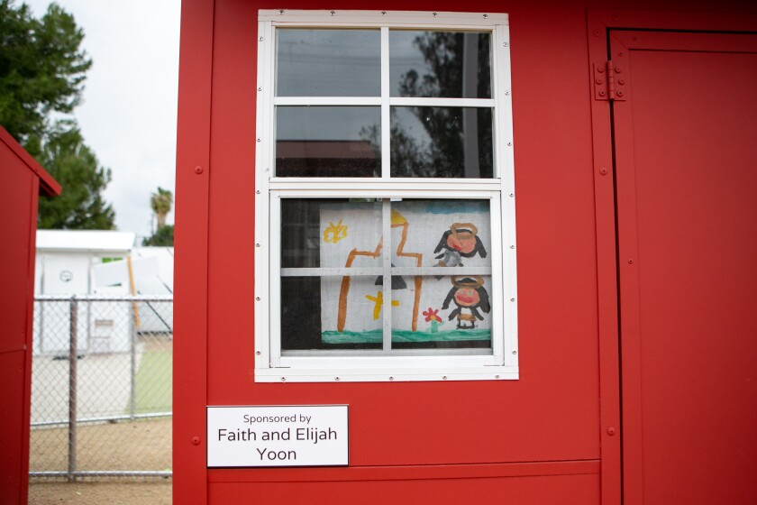 A child's painting of a house and a landscape decorates the window of a tiny home that is painted red