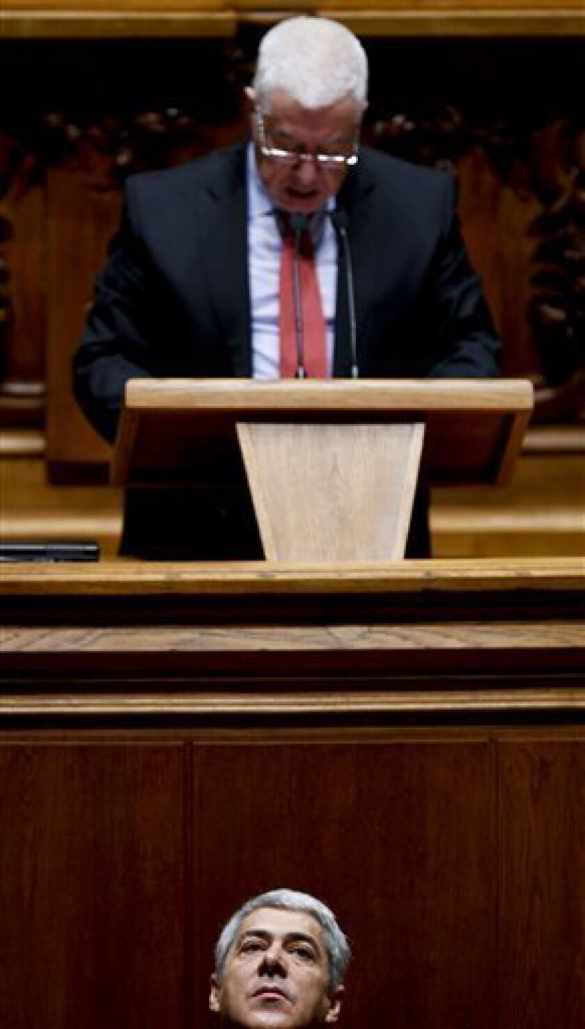 Portuguese Prime Minister Jose Socrates, bottom, looks up as Finance Minister Fernando Teixeira dos Santos, top, addresses to the Portuguese parliament during the final vote of his government's 2011 state budget on Friday, Nov. 26, 2010 in Lisbon. Portugal's Parliament has approved a plan to hike t