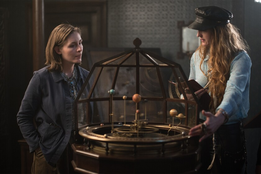 "On ""The Luminaries"" set, author Eleanor Catton and director Claire McCarthy flank a model of the solar system."