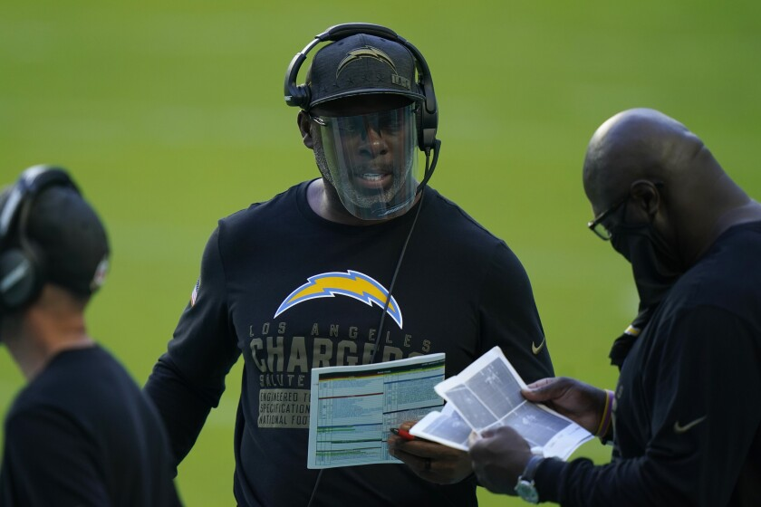 Chargers head coach Anthony Lynn, center, talks to his staff on the sidelines.