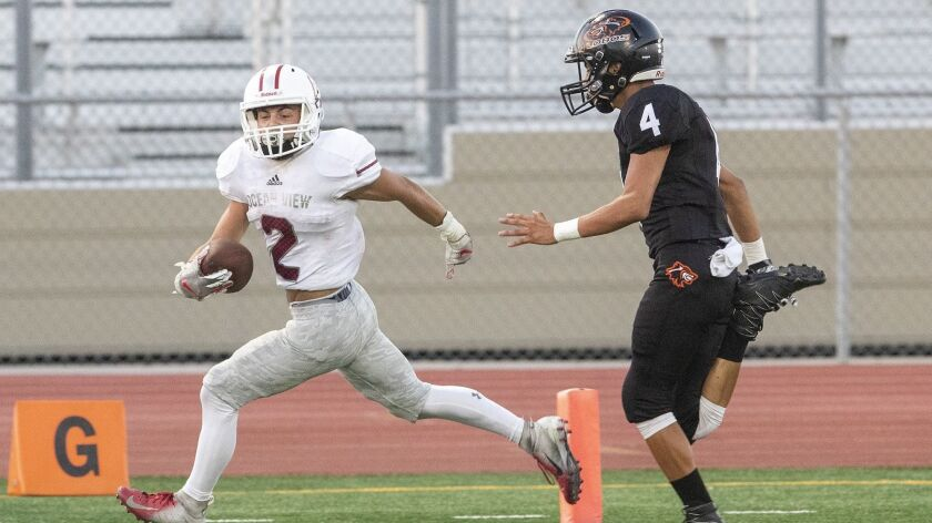 Ocean View's Will Earthman beats Los Amigos' Jesus Sanchez for a touchdown during a game at Garden
