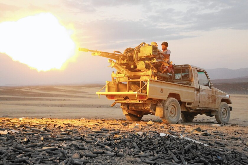 A member of the pro-government forces battling Houthi rebels unleashes machine-gun fire in Sirwah, Yemen.
