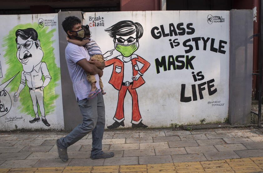 A man wearing a face mask as a precaution against the coronavirus carries a child and walks past a graffiti in Kochi, Kerala state, India, Saturday, Oct. 31, 2020. (AP Photo/R S Iyer)