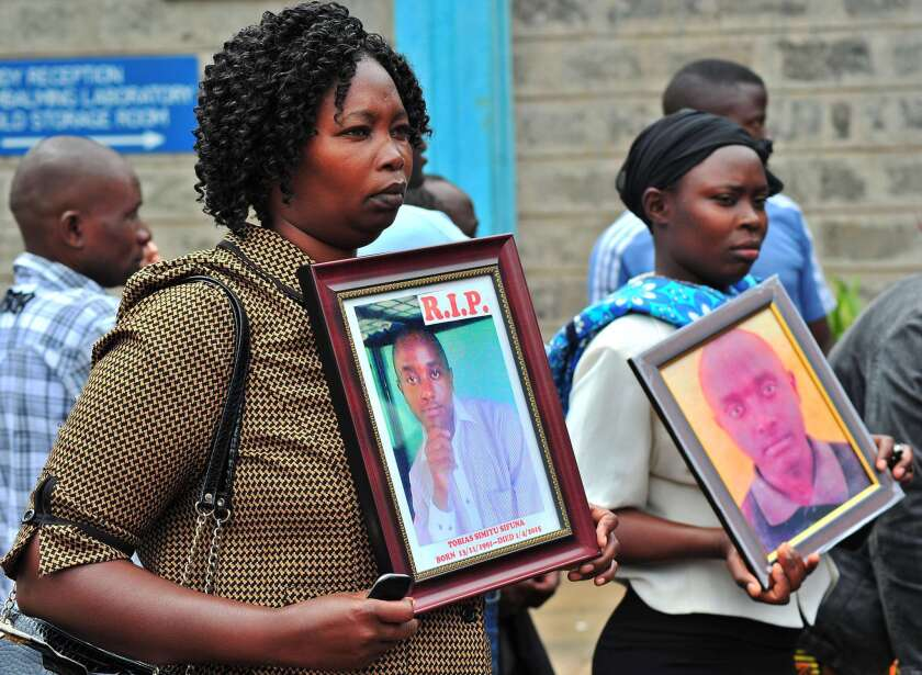 Relatives of those killed in the terror attack at Kenya's Garissa University College hold portraits of their kin on April 9 as they wait to retrieve victims' bodies from a morgue in Nairobi.