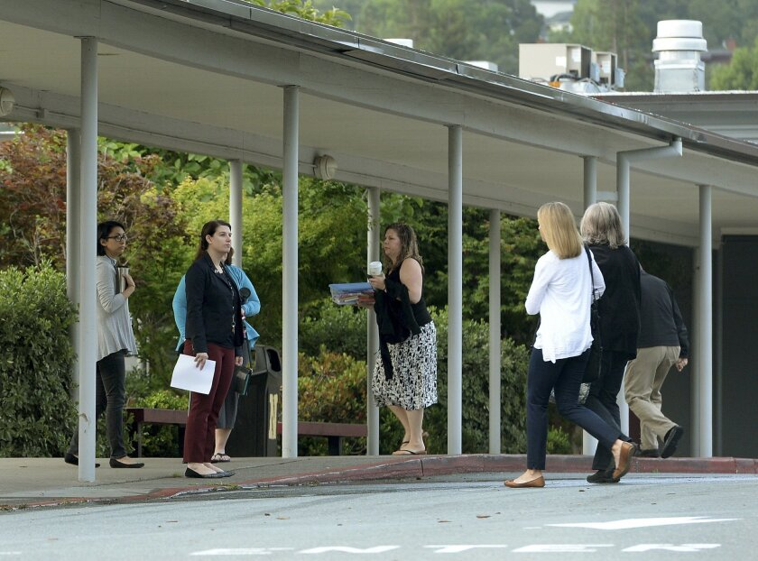 Novato High School staff members arrive at work Thursday, May 26, 2016, following at attack on two students in Novato, Calif. Attackers shot two students Wednesday near the San Francisco Bay Area high school, killing one and sending another to a hospital in an incident that prompted the closing of the campus to students. (Robert Tong/Marin Independent Journal via AP) MANDATORY CREDIT