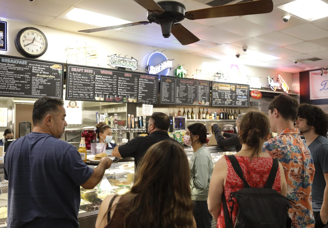 People wait to order a sandwich at a restaurant counter.