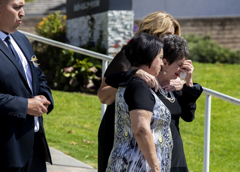 Family members grieve as the casket of 6-year-old Aiden Leos is put into a hearse.