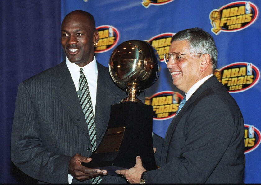FILE - In this June 18, 1996, file photo, Chicago Bulls' Michael Jordan, left, receives the NBA Finals Most Valuable Player trophy from Commissioner David Stern during a ceremony in Chicago. David Stern, who spent 30 years as the NBA's longest-serving commissioner and oversaw its growth into a global power, has died on New Year's Day, Wednesday, Jan. 1, 2020. He was 77. (AP Photo/Charles Bennett, File)
