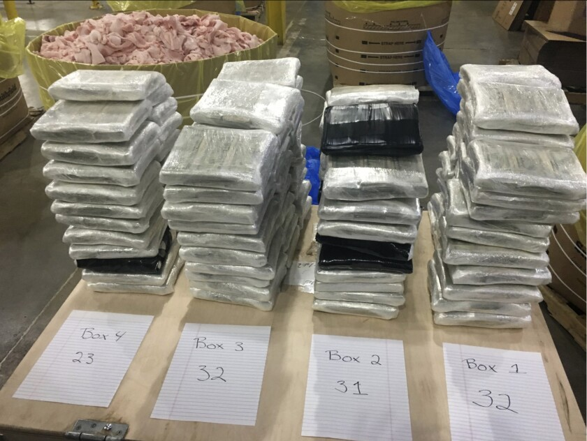 In this December 2019 photo provided by the Cleveland County Sheriff's Office in Shelby, N.C., approximately $3 million in cash, wrapped in plastic, is displayed near the barrels of raw pork shoulder in which it was discovered in. North Carolina deputies recovered the barrels Saturday, Dec. 7, 2019, from a tractor trailer they pulled over. (Cleveland County Sheriff's Office via AP)