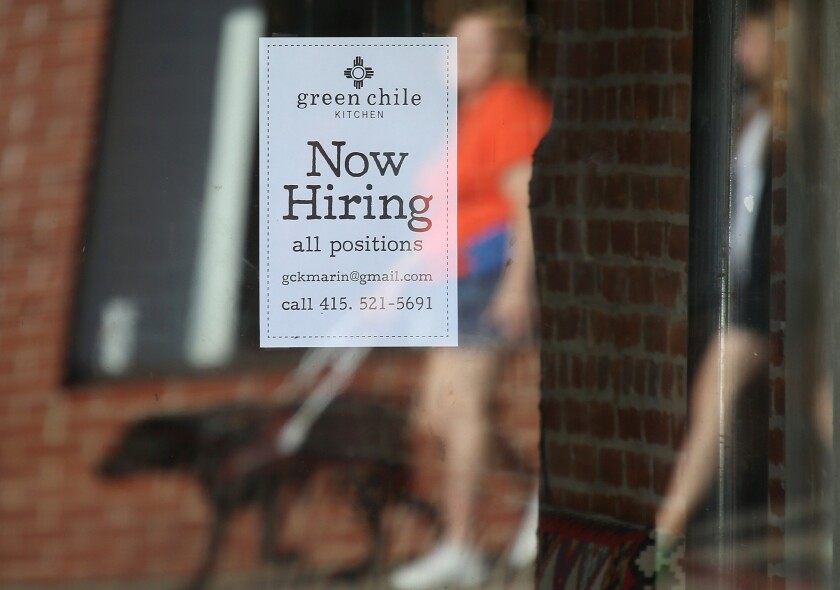"""Pedestrians walk by a """"Now Hiring"""" sign posted in a store window of a business in San Rafael, Calif., on Nov. 7."""