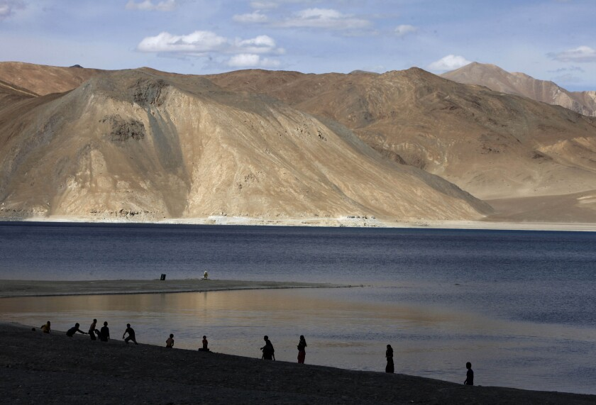 In this July 22, 2011 file photo, people stand by the banks of the Pangong Lake, near the India-China border in Ladakh, India.Indian officials say Indian and Chinese soldiers are in a bitter standoff in the remote and picturesque Ladakh region, with the two countries amassing soldiers and machinery near the tense frontier. The officials said the standoff began in early May when large contingents of Chinese soldiers entered deep inside Indian-controlled territory at three places in Ladakh, erecting tents and posts. (AP Photo/Channi Anand, File)