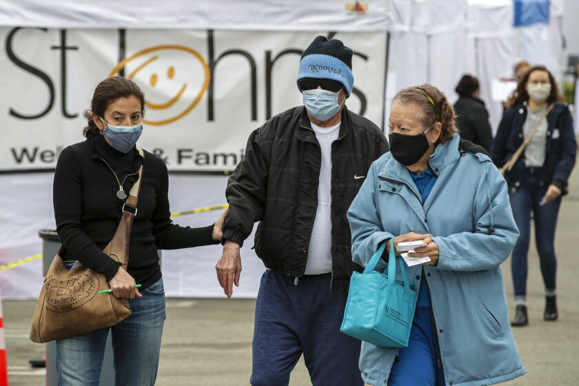 People walk to a COVID-19 vaccination site in East Los Angeles.