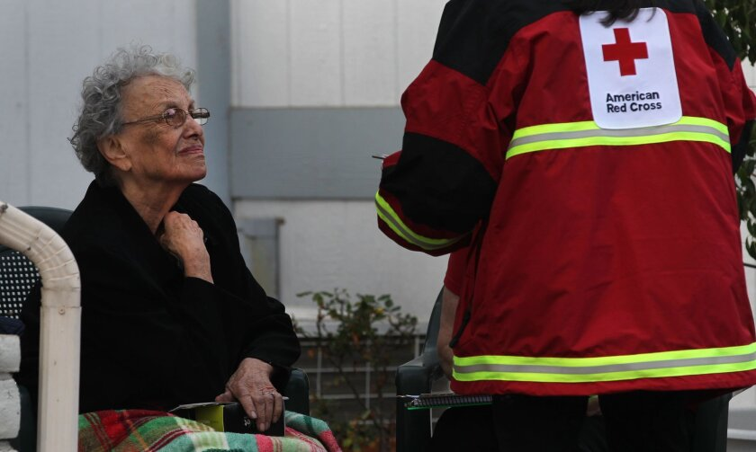 Newspaper delivery man Eduardo Barajas called 911 and help79 year-old Sarah Erman, shown here talking to Red Cross workers, was burned out of her mobile home in Otay early Thursday morning by an arson fire.