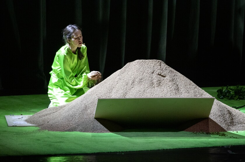 A kneeling woman sifts sand through her hands on a stage bathed in green.