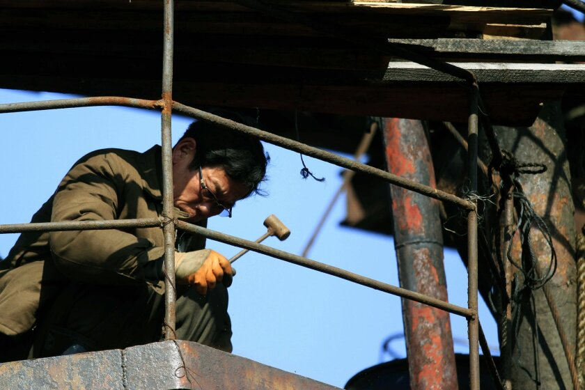 "In this March 12, 2016 photo, a shipbuilder works with a hammer at Hongwon Shipyard in Hongwon County, South Hamgyong Province, North Korea. North Koreans are being mobilized en masse to boost production and demonstrate their loyalty to leader Kim Jong Un in a 70-day campaign aimed at wiping out ""indolence and slackness."" (AP Photo/Jon Chol Jin)"