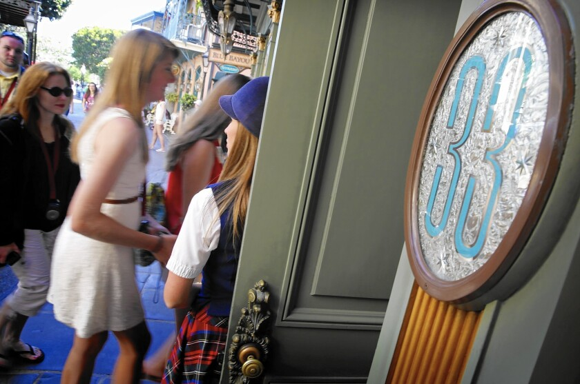 Victoria Dale, guest relations guide, holds open the door to the Club 33 restaurant for visitors on a special paid VIP tour at Disneyland in 2013.